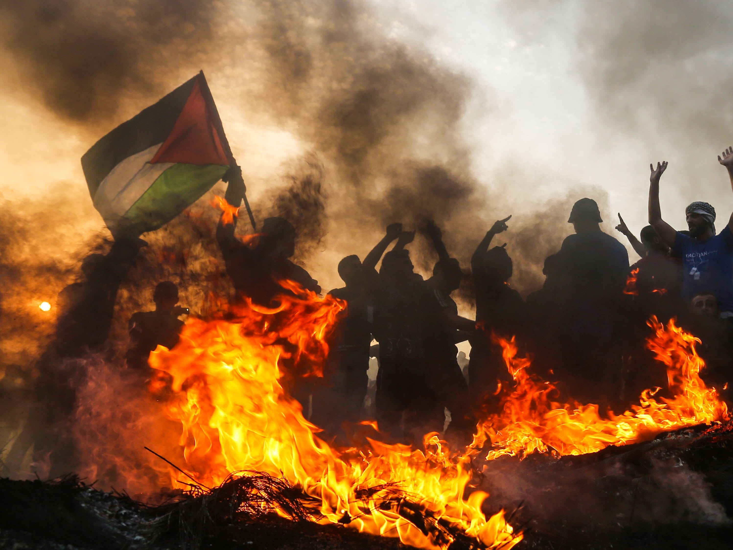 A Palestinian protester waves a national flag during a demonstration on the beach near the maritime border with Israel, in the northern Gaza Strip, on Oct. 22, 2018.