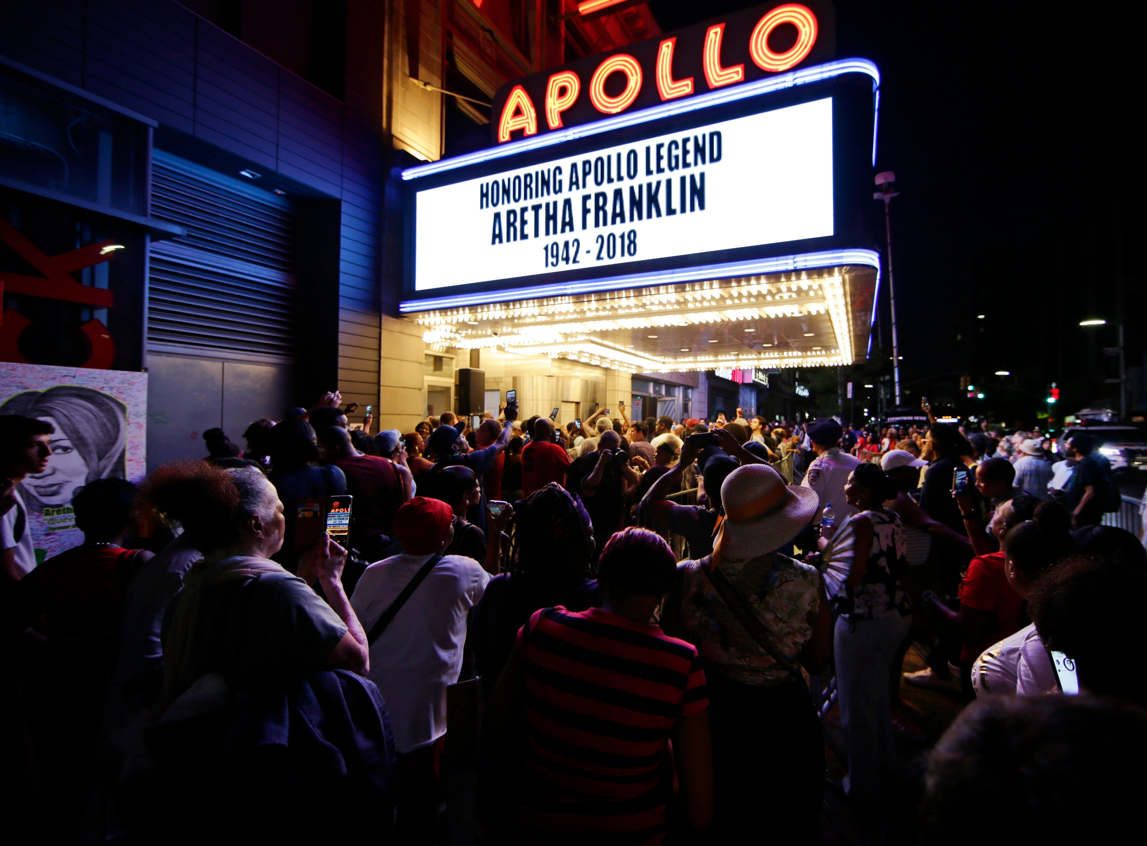 Aug. 16, 2018: People gather near a makeshift memorial for singer Aretha Franklin outside the Apollo Theater in New York. Franklin died Thursday in her home in Detroit at age 76 from pancreatic cancer.
