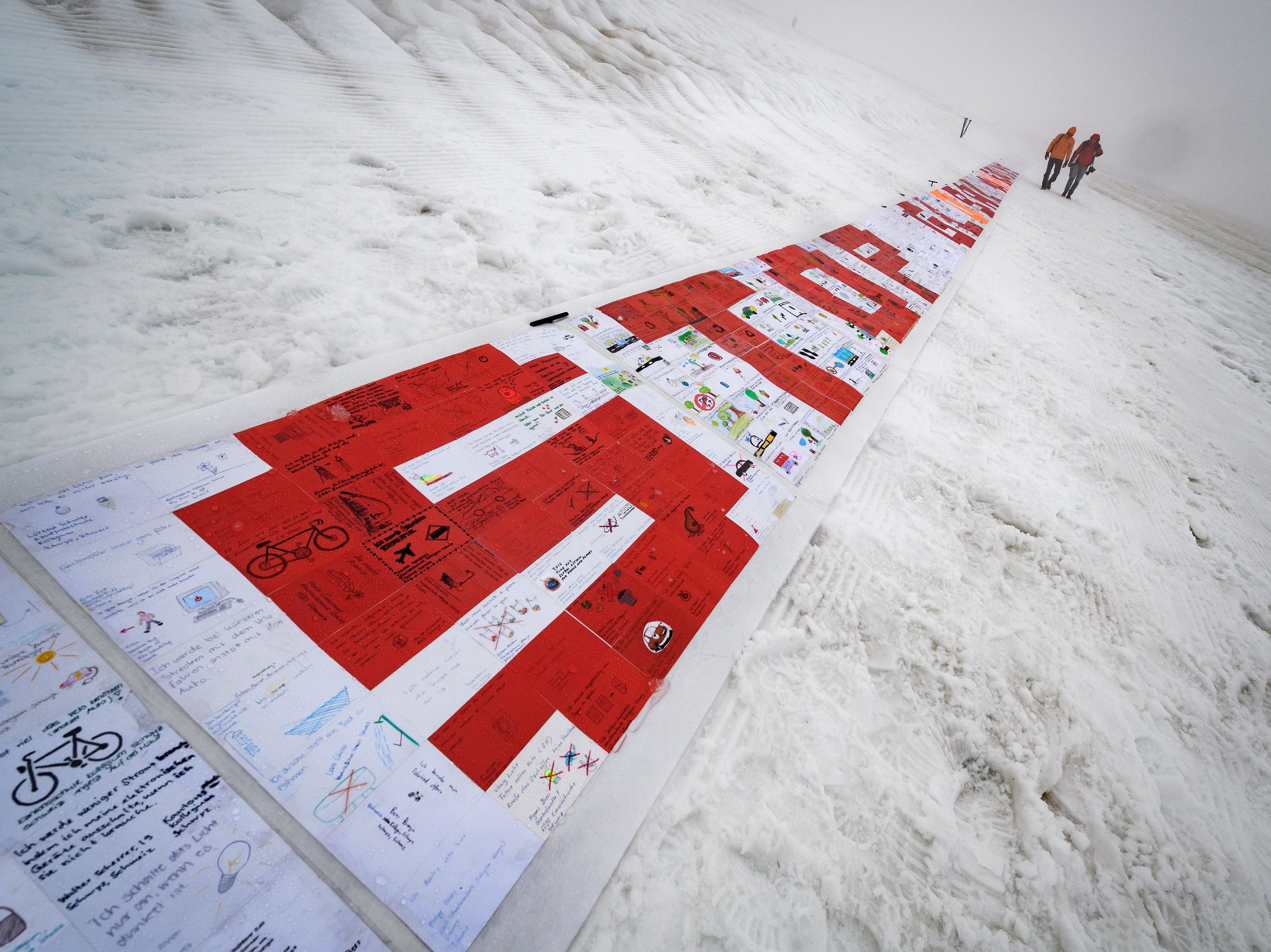 Aug. 13, 2018: Organizers walks past a giant roll made up of more than 2500 laminated postcards, put together to make up a message against climate change, during a test to see how to deploy the banner, in the Aletsch Glacier near the Jungfraujoch in the Swiss Alps. The test was organized to prepare a world record attempt of the largest postcard on the Alps longest glacier to kick off a global youth climate movement. Swiss Agency for Development and Cooperation  along with the WAVE foundation expect to create the largest postcard made up of at least 100,000 standard sized postcards.