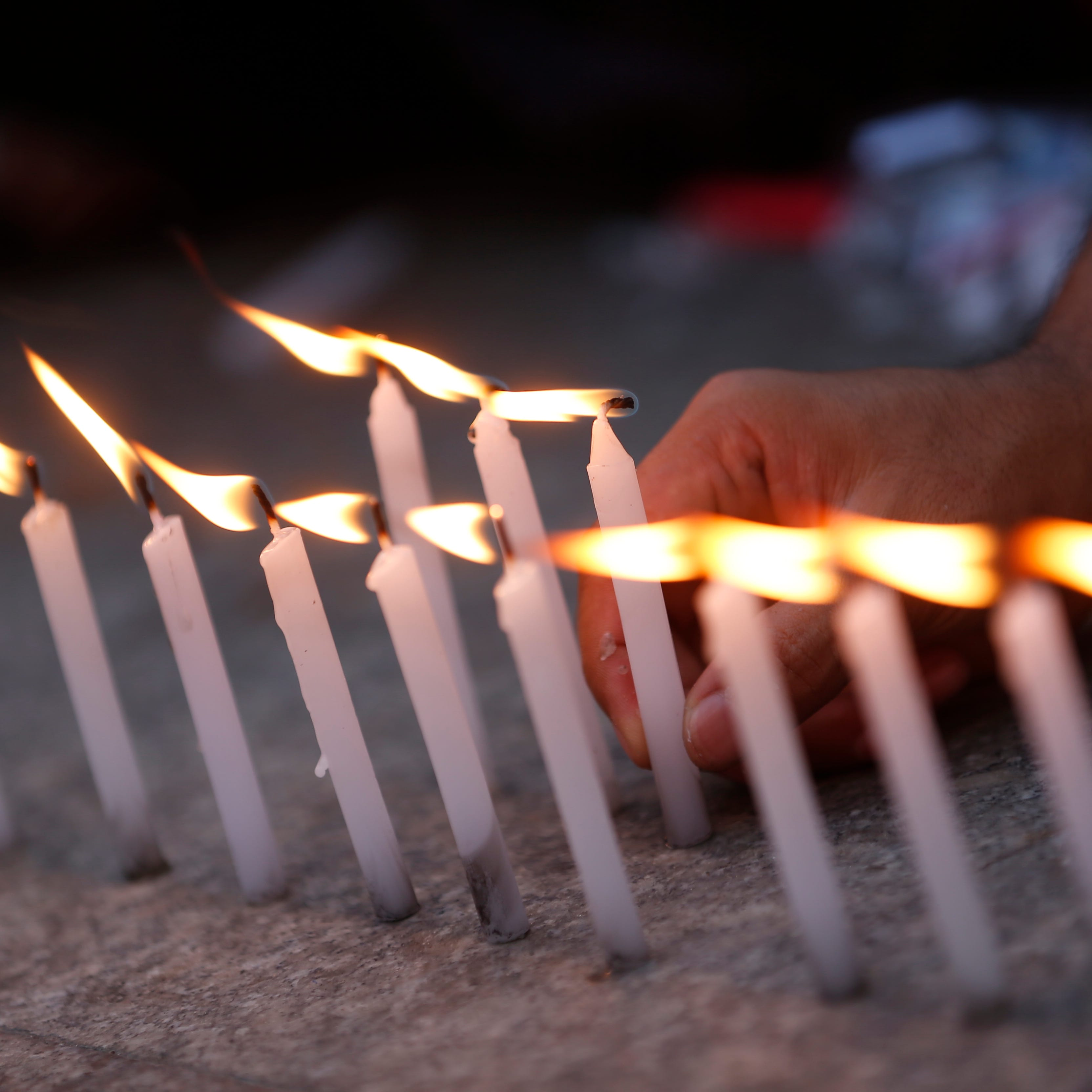 A demonstrator lights candles during a demonstration to mark the one-year anniversary of the arrest and detention of Reuters journalists Wa Lone and Kyaw Soe Oo in Myanmar.