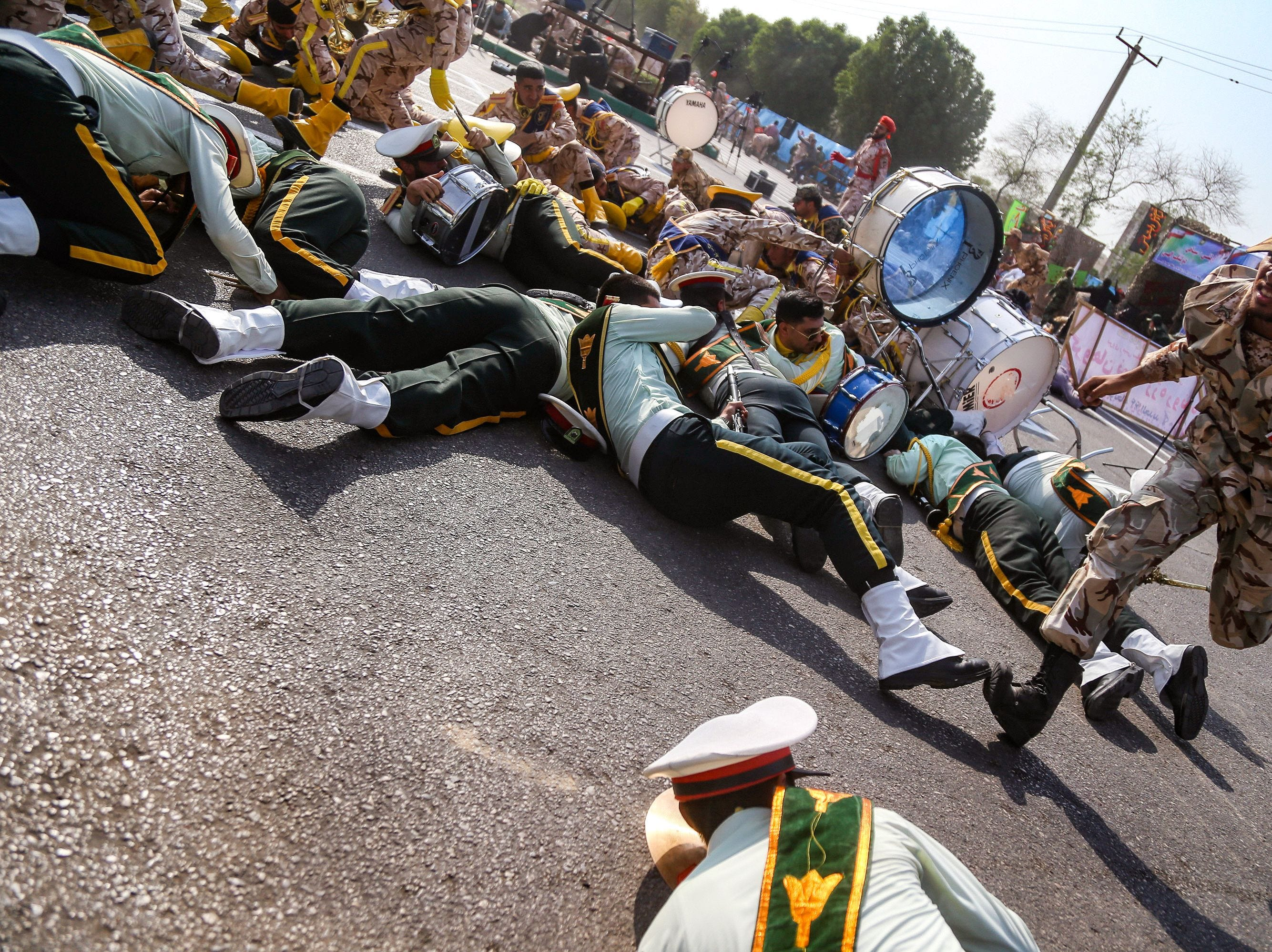 A soldier runs past injured comrades lying on the ground at the scene of an attack on a military parade in Ahvazm Iran that was marking the anniversary of the outbreak of its devastating 1980-1988 war with Saddam Hussein's Iraq on Sept. 22, 2018.