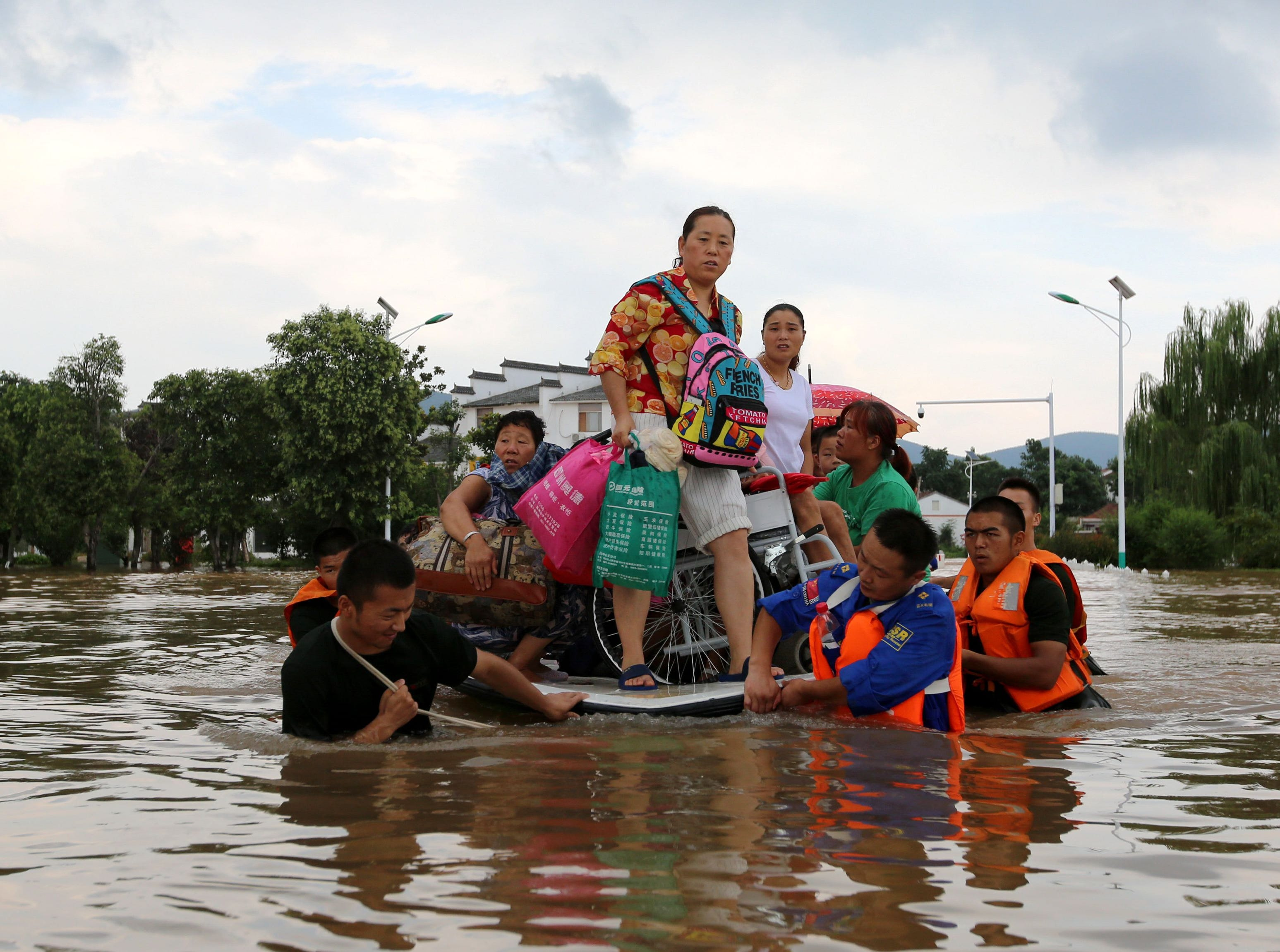 Aug. 19, 2018: Rescuers evacuate residents through floodwaters after heavy rainfall caused by Typhoon Rumbia in Huaibei, China.