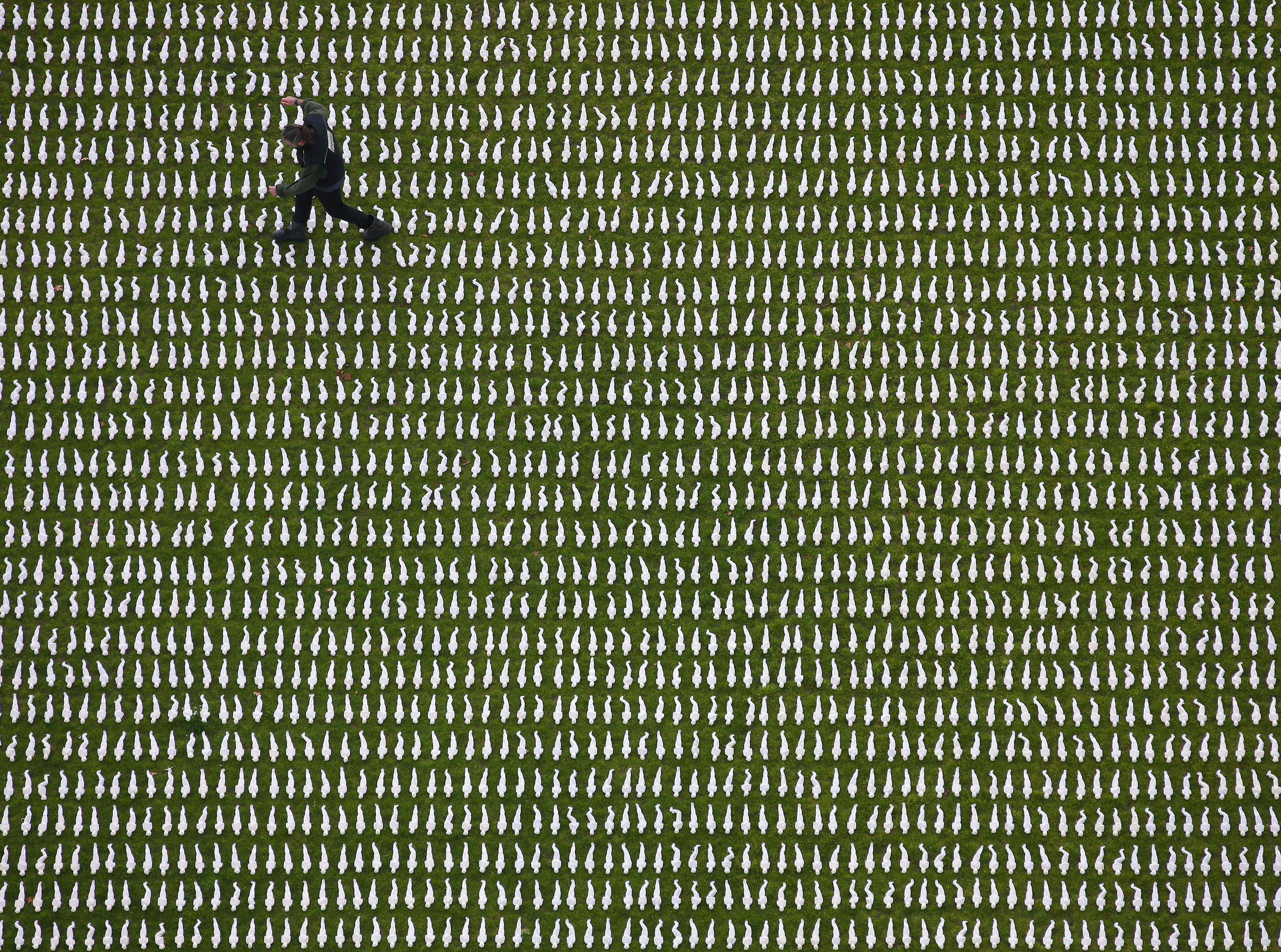 """British artist Rob Heard poses for a photograph amongst 72,396 shrouded figures, which form his installation """"Shrouds of the Somme"""", laid out at the Queen Elizabeth Olympic Park in London on Nov. 7, 2018, to represent Commonwealth servicemen who died at the Somme, and who have no known grave. The 12-inch shrouded figures have been laid out by volunteers and members of the British Army's 1 Royal Anglian Regiment to mark the 100th anniversary of the end of the First World War."""