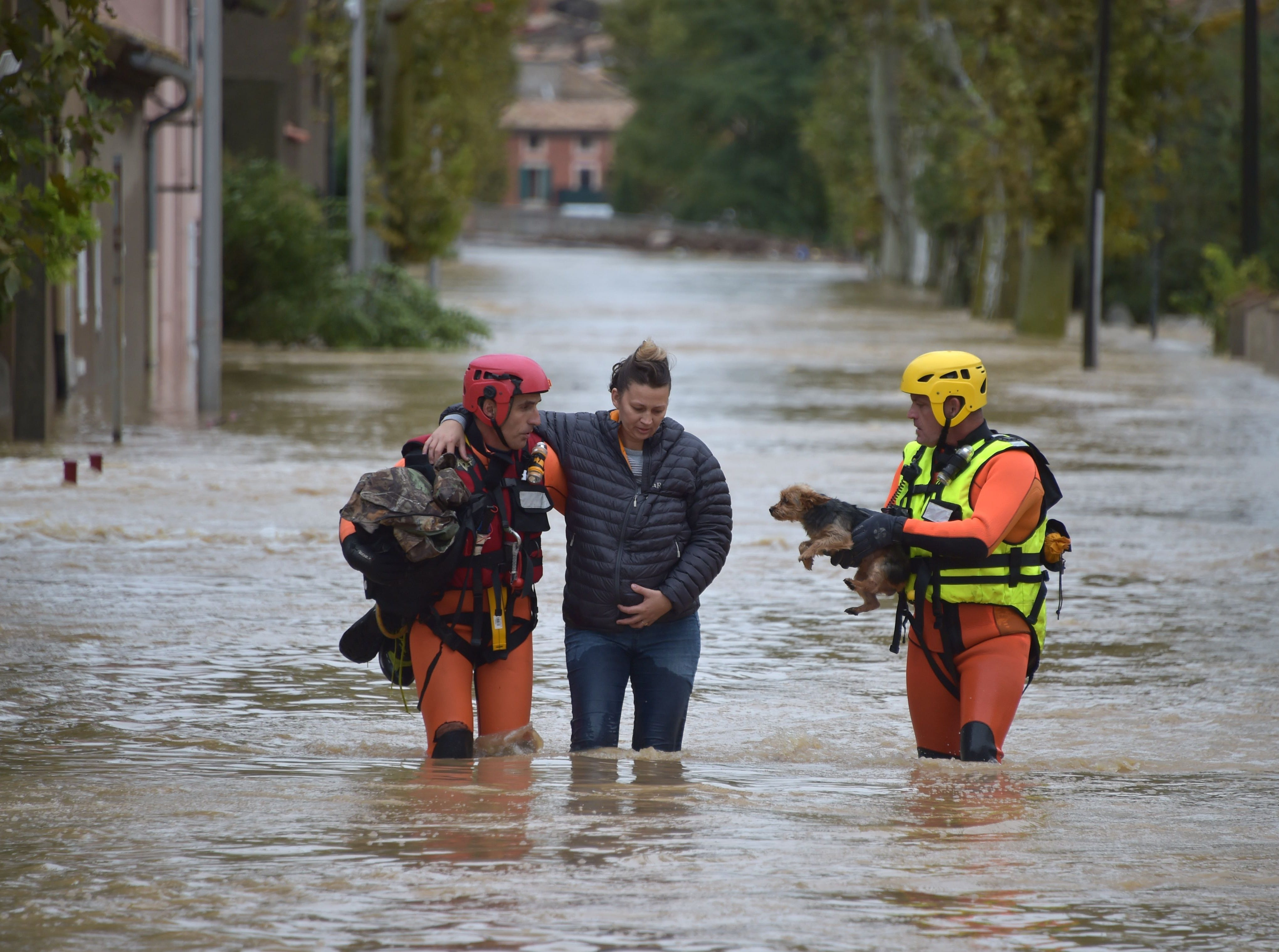 Firefighters help a resident with a dog following heavy rains that saw rivers bursting banks on Oct. 15, 2018 in Trebes, near Carcassone, France.