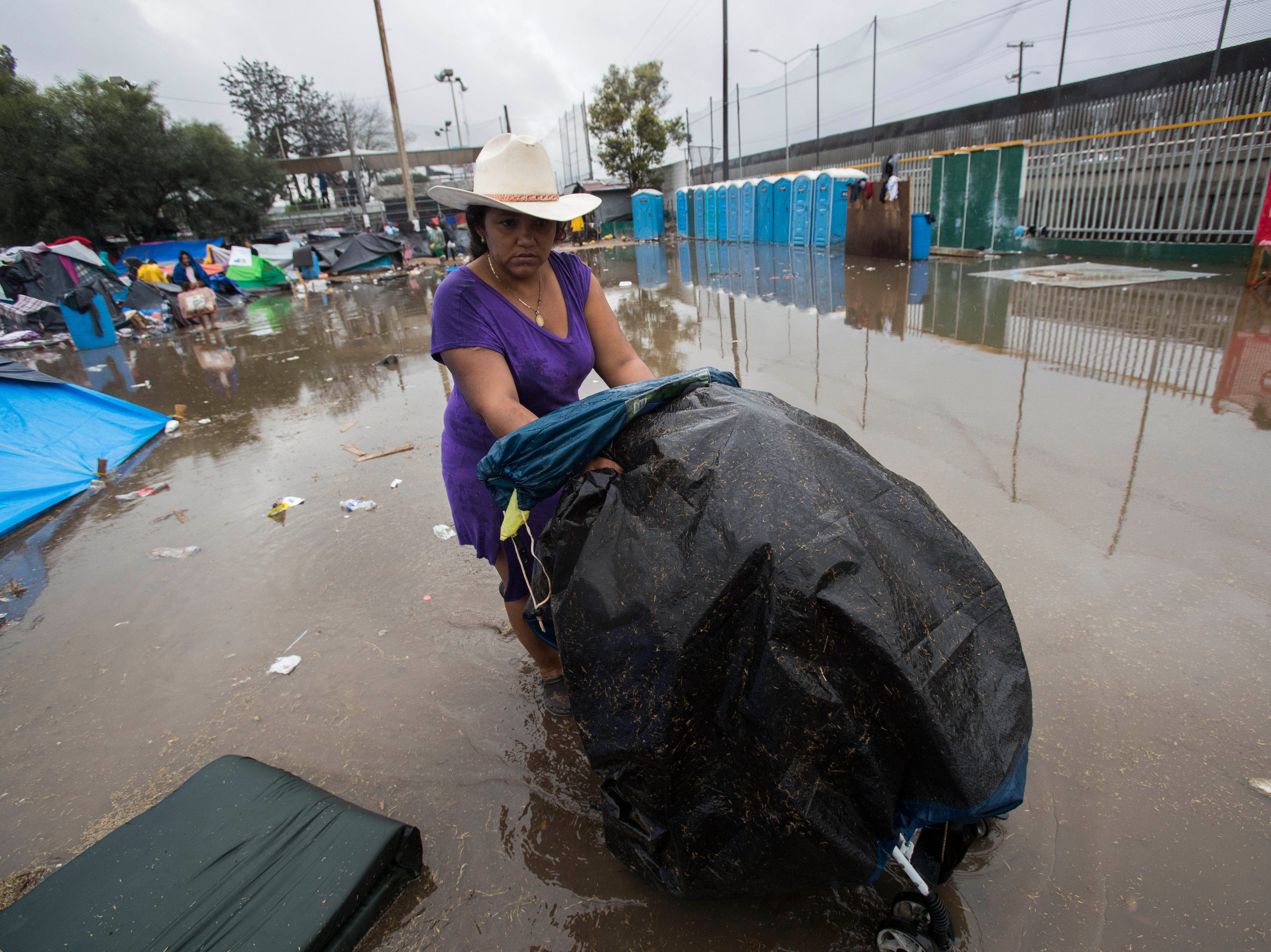 A a woman pushing a stroller holding her belongings through dirty water in Tijuana, Mexico on Nov. 29, 2018. The Benito Juarez sports complex, which is serving as a shelter for over 5000 caravan migrants, was drenched with heavy rains, causing already precarious living conditions to worsen.