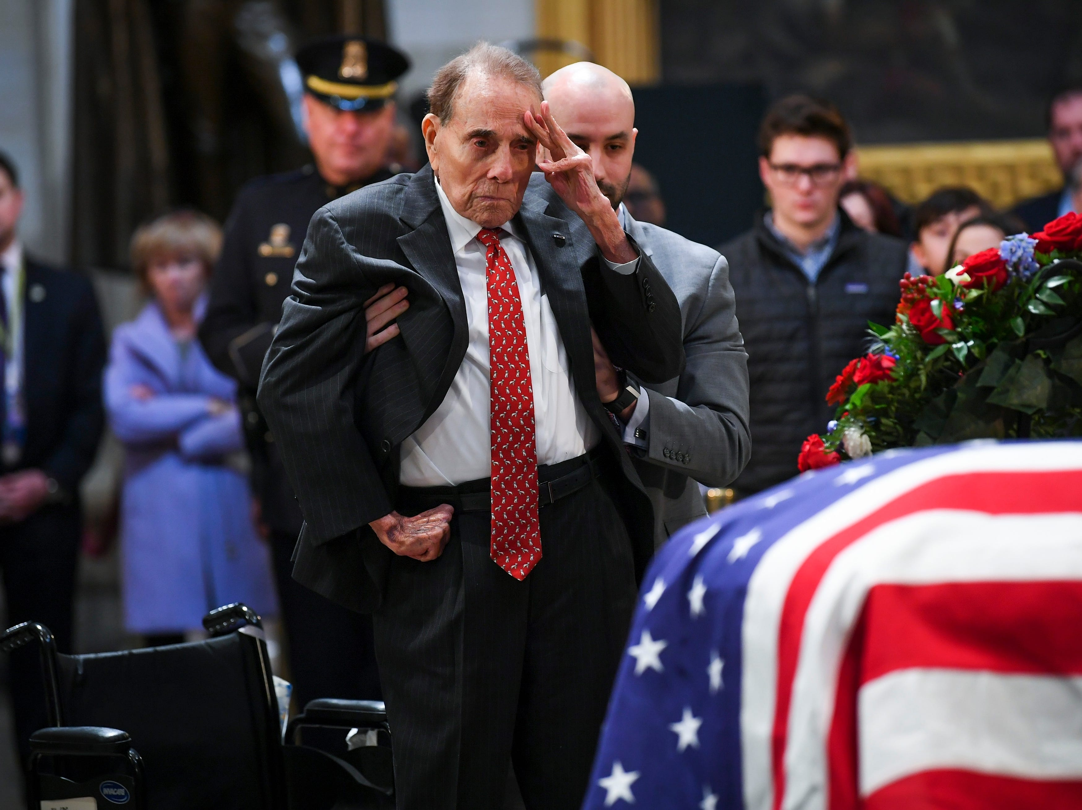 Former Sen. Bob Dole stands and salutes the casket of President George H.W. Bush who lies in state at the U.S. Capitol Rotunda on Dec. 4, 2018.