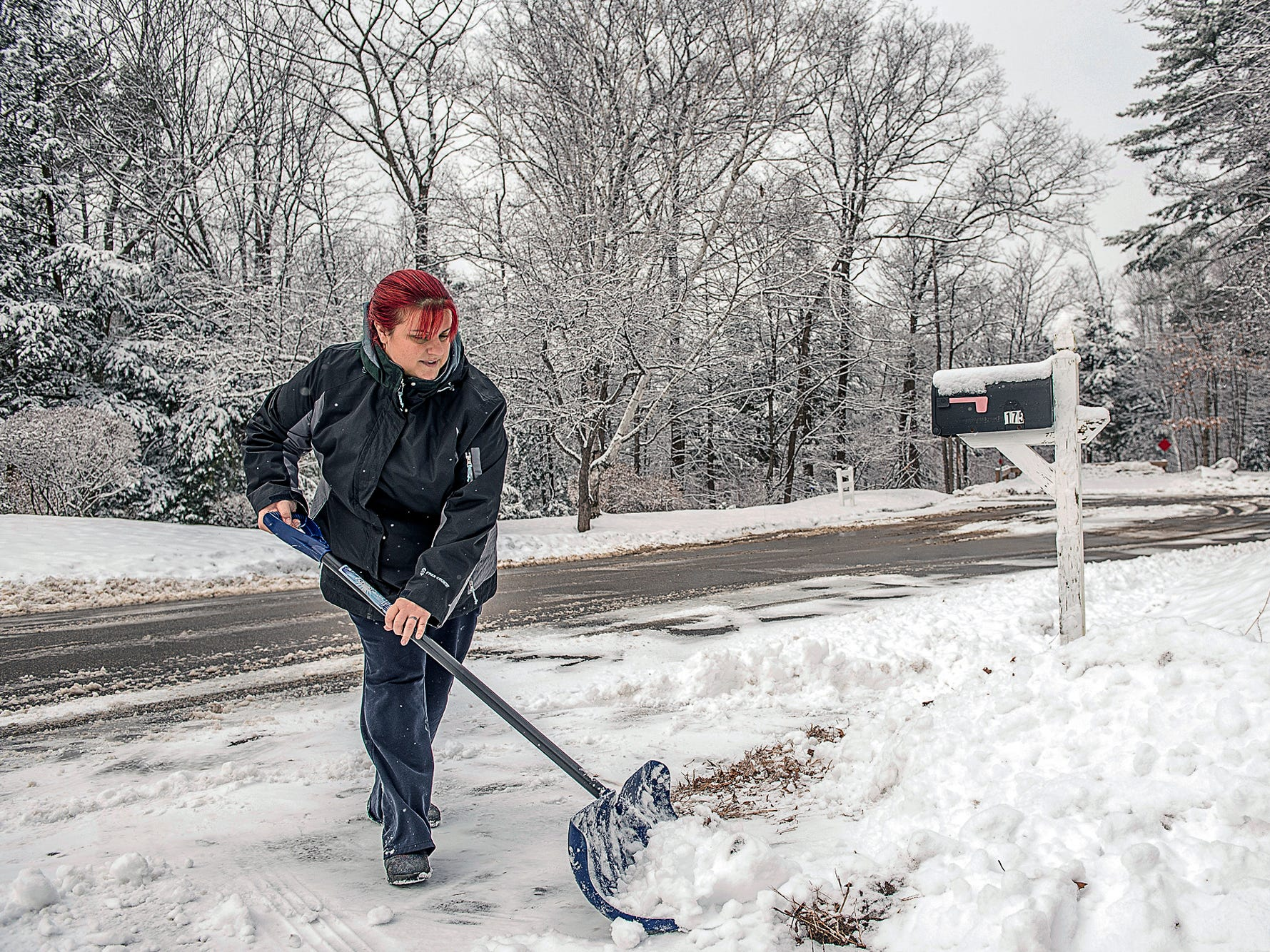 "Jessica Ireland shovels snow from her driveway, Monday, Dec. 17, 2018, in Auburn, Maine. She said, ""Yesterday I was raking leaves!"" And she said her teenaged children are excited about a having a white Christmas. (Andree Kehn/Sun Journal via AP) ORG XMIT: MELEE101"