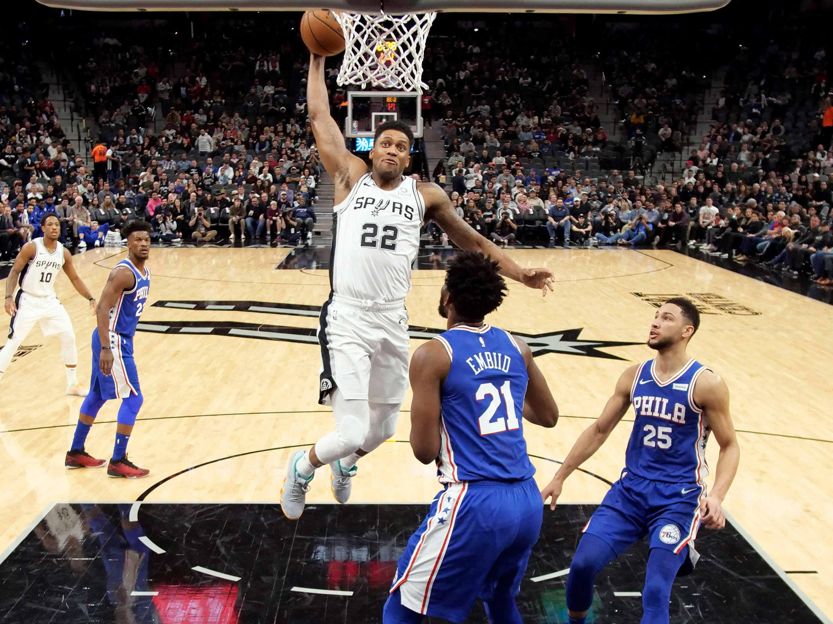 Dec. 17: Spurs small forward Rudy Gay goes in for a dunk as 76ers center Joel Embiid looks on during the first half at AT&T Center.