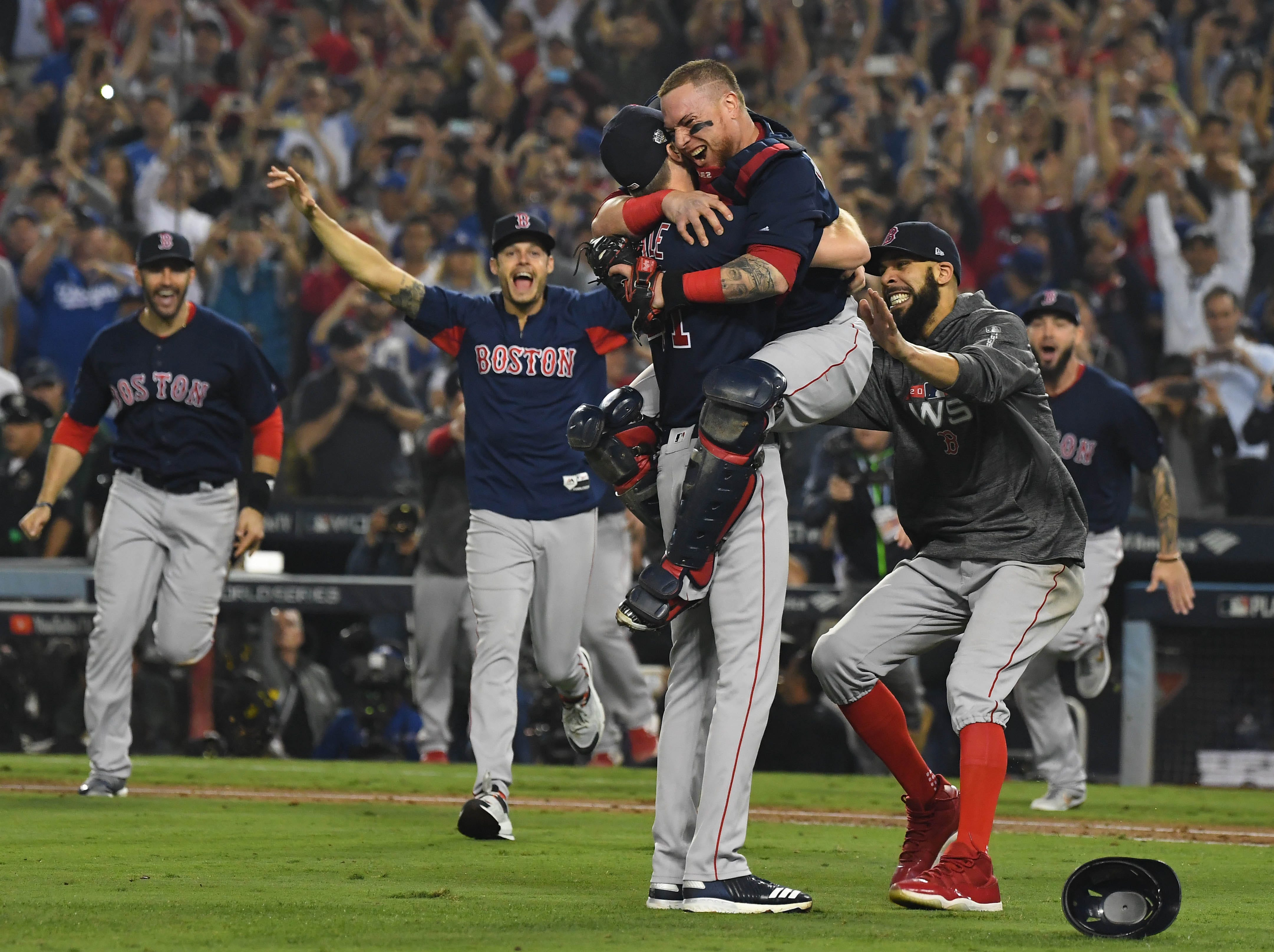 Boston Red Sox pitcher Chris Sale (left) celebrates with teammates including catcher Christian Vazquez and pitcher David Price (right) after defeating the Los Angeles Dodgers in game five of the 2018 World Series at Dodger Stadium on Oct. 28, 2018.