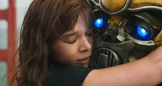 """Charlie (Hailee Steinfeld) shares a hug with her mechanized best friend in """"Bumblebee."""""""