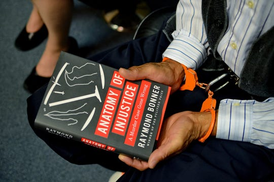 Edward Lee Elmore holds a copy of a book about his case on Friday, March 2, 2012 in Greenwood, S.C.   Elmore, who spent 30 years in prison for murdering Dorothy Edwards, a crime that Elmore said he did not commit, was set free by Judge Frank Addy on Friday.  (AP Photo/ Richard Shiro)