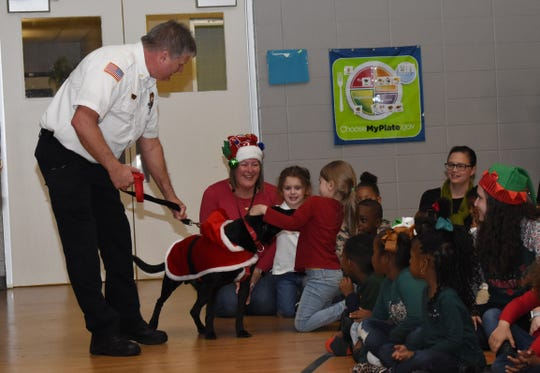 Assistant fire chief for the Alexandria Fire Department, Jeff Tarver, lets Mabel Brasher Montessori Elementary School students pet K9 Nitro, a search and rescue dog for the department. The Alexandria Academy Sports + Outdoors surprised 30 Mabel Brasher Montessori Elementary School students with bicycles and helmets Wednesday, Dec. 19, 2018. Alexandria Fire Station 5 firefighters were also onhand to meet the students. The Mabel Brasher students were among the 5,000 students in 16 states that were given bikes as part of Academy's holiday bike donation program. The bikes are a reward for children who have perfect attendance, academic performance, good behavior and may have a need for the gift.