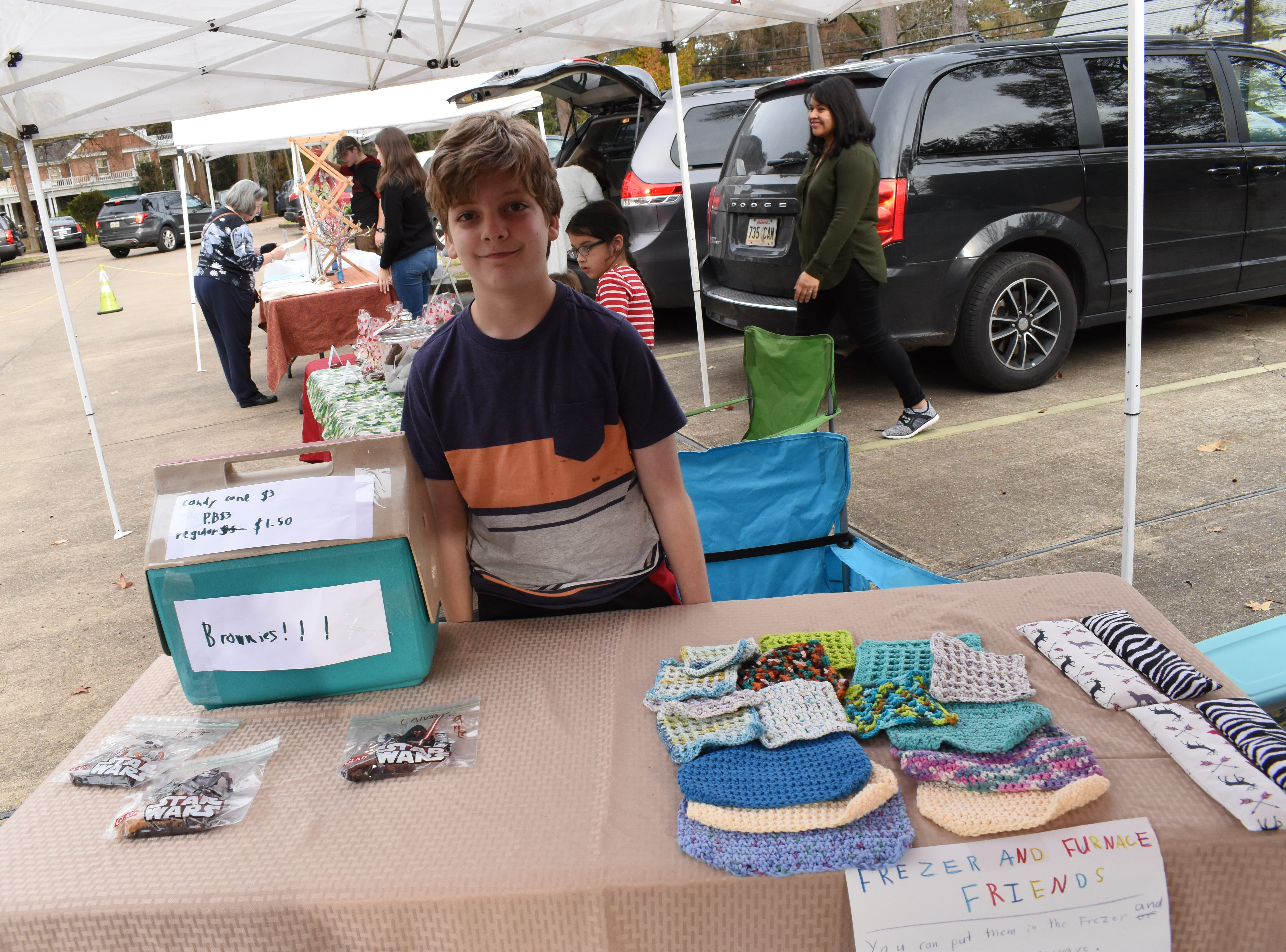 "On Tuesday, Dec. 18, 2018, children set up mini-booths at the Alexandria Farmers Market ""Holiday Market"" to sell items they made. About 10 booths were manned by 23 children. The youngest was four and the oldest was 15. The mini-vendors were selling items such as wooden ornaments and crafts; soaps, hair products; jewelry; locally grown turnips and mustard greens; wands; cookies and sweets; embroidered kitchen towels; burp rags, cotton wash cloths, and freezer/furnace friends which are rice filled cloth bags for aches or pains. Allison Tohme, market manager, said this was the first time the mini-vendors would be able to accept credit cards through the market's welcome booth and support from the Central Louisiana Economic Development Alliance (CLEDA). The Alexandria Farmers Market is held from 3-6 p.m. every Tuesday in the parking lot on Jackson Street across from First United Methodist Church located at 2727 Jackson Street."