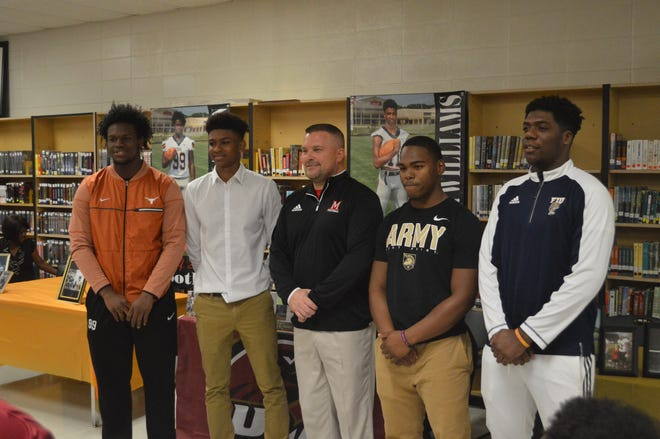 Many coach Jess Curtis poses with his four players after they signed to schools Wednesday. From left are: Myron Warren, Tavier Williams, Curtis, Shacori Williams and Ni'Kendrick Carter.