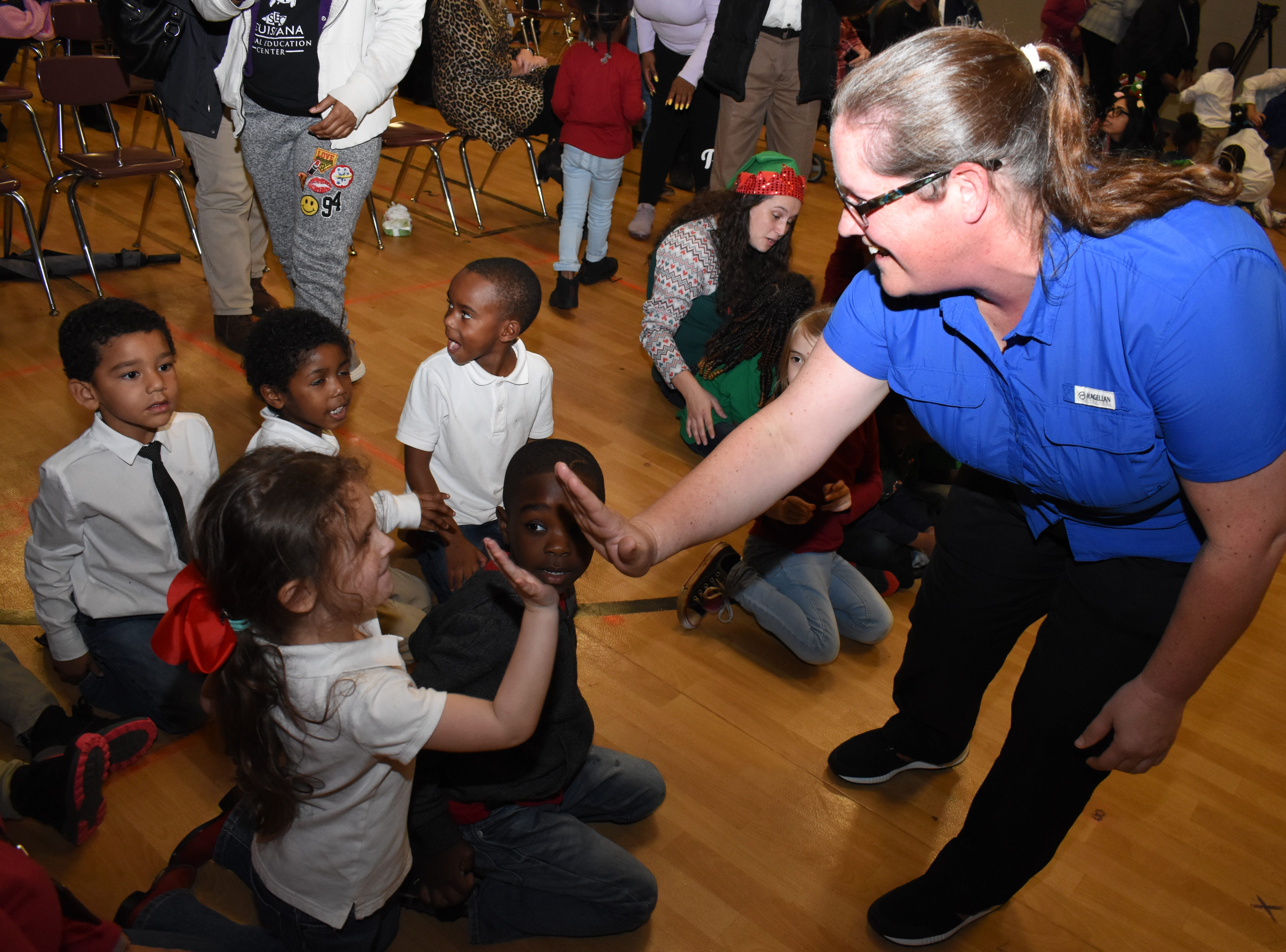 Laurie Meche, operations manager at the Alexandria Academy Sports + Outdoors, high-fives Mabel Brasher Montessori Elementary School students after Academy surprised 30 Mabel Brasher  students with bicycles and helmets Wednesday, Dec. 19, 2018. The Mabel Brasher students were among the 5,000 students in 16 states that were given bikes as part of Academy's holiday bike donation program. The bikes are a reward for children who have perfect attendance, academic performance, good behavior and may have a need for the gift.