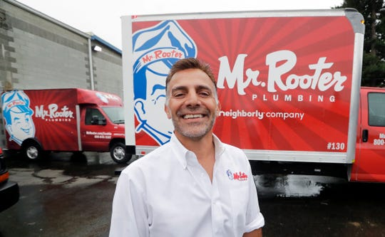 "Mr. Rooter Plumbing franchise owner Vinnie Sposari stands with one of his company's trucks in Seattle. As business owners struggle to fill job openings, they're changing their company culture to attract talented candidates. Sposari has made his Mr. Rooter Plumbing franchise in Seattle more employee-focused, adding benefits and perks because ""our trade is a dying breed."""