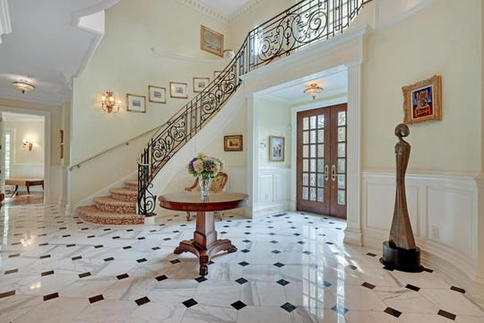 The foyer offers marble tile flooring and custom staircase.