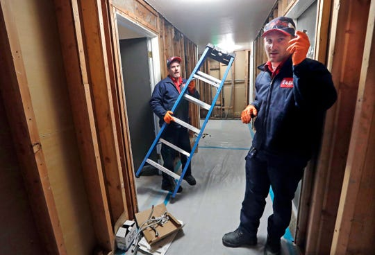 Veteran plumber Dale Baker, left, and his trainee Danny Stanke walk through a hallway of an apartment building where they are replacing the plumbing, in Seattle. Stanke is on a multi-year training program with the company, a Mr. Rooter Plumbing franchise.