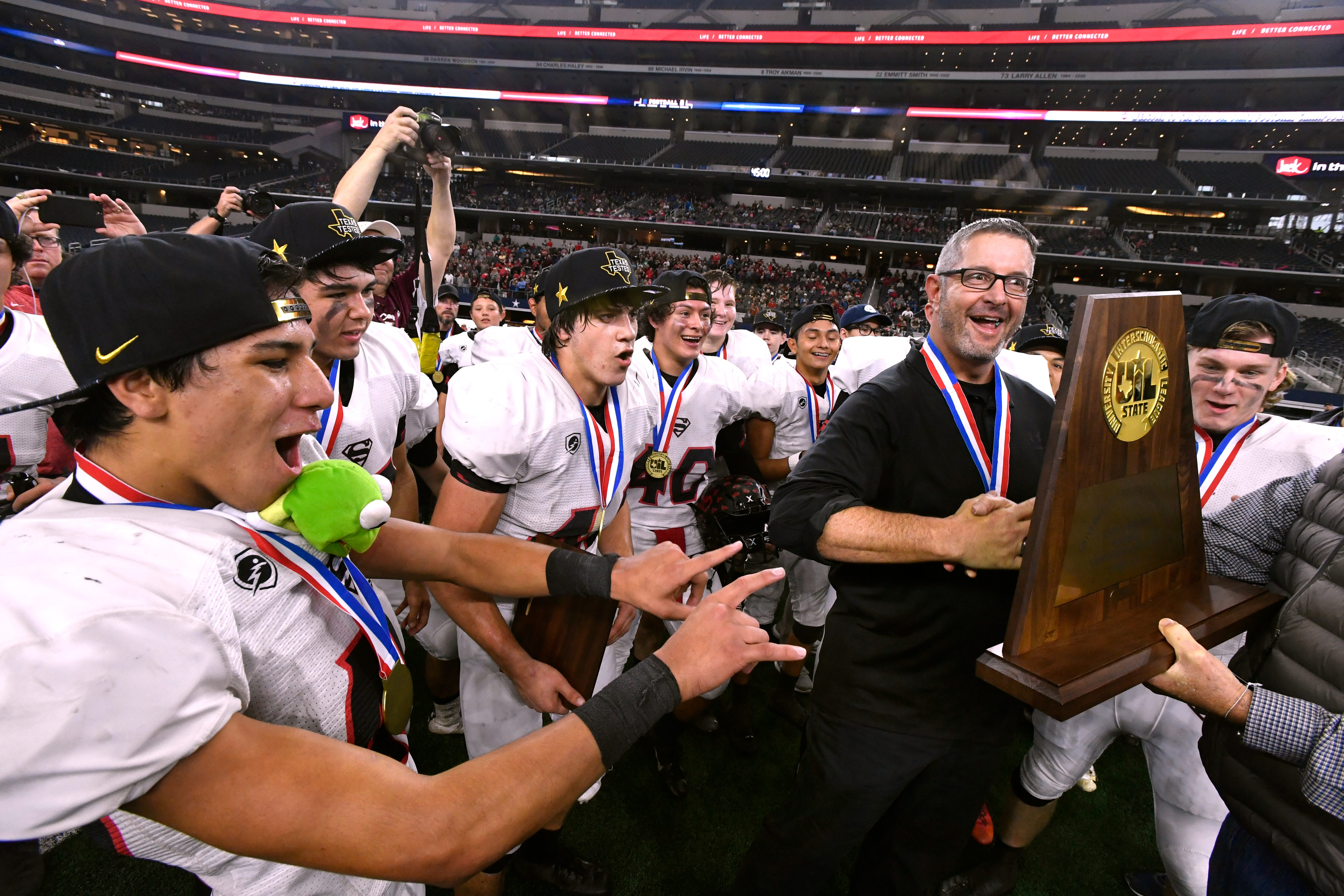 Strawn head coach Dewaine Lee is surrounded by his team as he accepts the Class 1A Division II championship trophy Dec. 19 at AT&T Stadium.