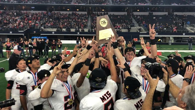 The Strawn football team celebrates winning its second-straight Class 1A Division II state championship by raising the UIL trophy with two fingers in the air.