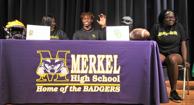 Merkel's Jonah White, near left, gives the Baylor Bears' claw sign after signing to play football for the Bears on Wednesday, Dec. 19, 2018, while being surrounded by family members at Merkel High School.