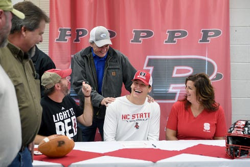 Kameron Walker, seated between his parents Rick and Karen Henson, is congratulated by one of his former coaches and youth minister Kevin Valentine after signing to play with North Carolina State University in a ceremony at Pisgah High School on Dec. 19, 2018.