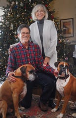 Orchard Inn owners Marc and Marianne Blazar pose in front of their Christmas tree  with dogs Murray, age 7, left, and Clayton, age 3.