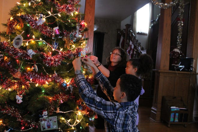 Kindra Hanson and her adopted children, Jadyn, 11, and Devon, 13, fix their Christmas tree.
