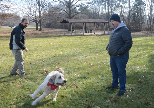 Jeff Breedlove and Michael Delaware, exercise Moka, Delaware's St. Bernarddoodle Wednesday at a proposed dog park at Bailey Park.