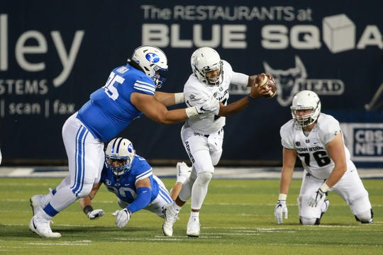 Utah State Aggies quarterback Kent Myers (2) tries to get away from Brigham Young Cougars defensive lineman Khyiris Tonga (95) during the second half at Merlin Olsen Field at Maverik Stadium.