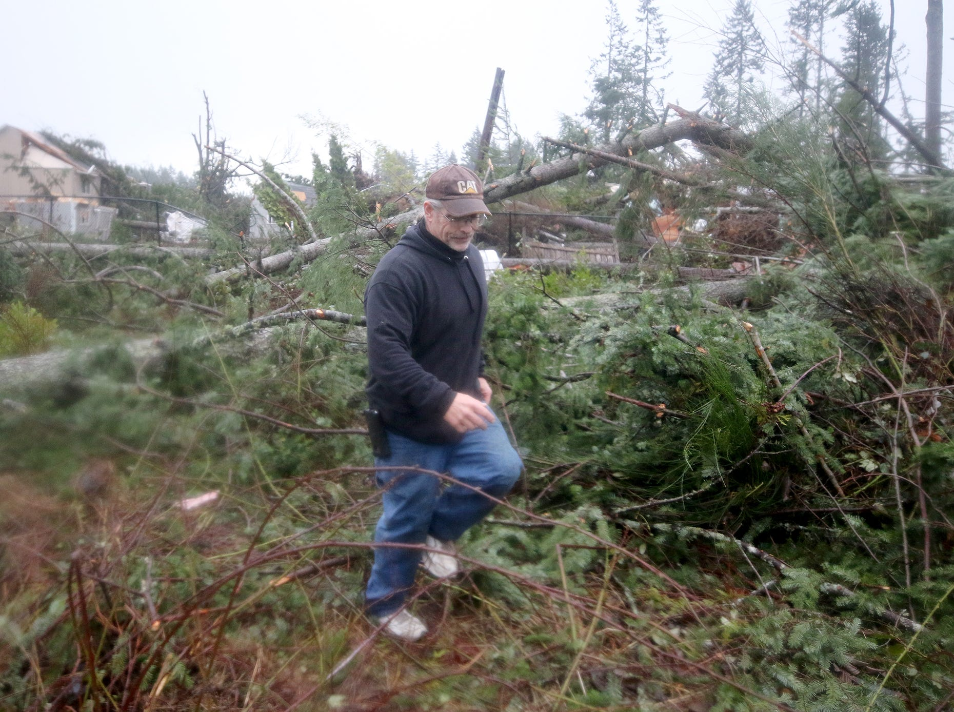 Matt Hargis walks through the downed trees behind Walmart after A tornado came through Port Orchard on the afternoon of Tuesday, December 18, 2018. The path was over Bethel near Walmart, and Safeway. He filmed the tornado from the Safeway.