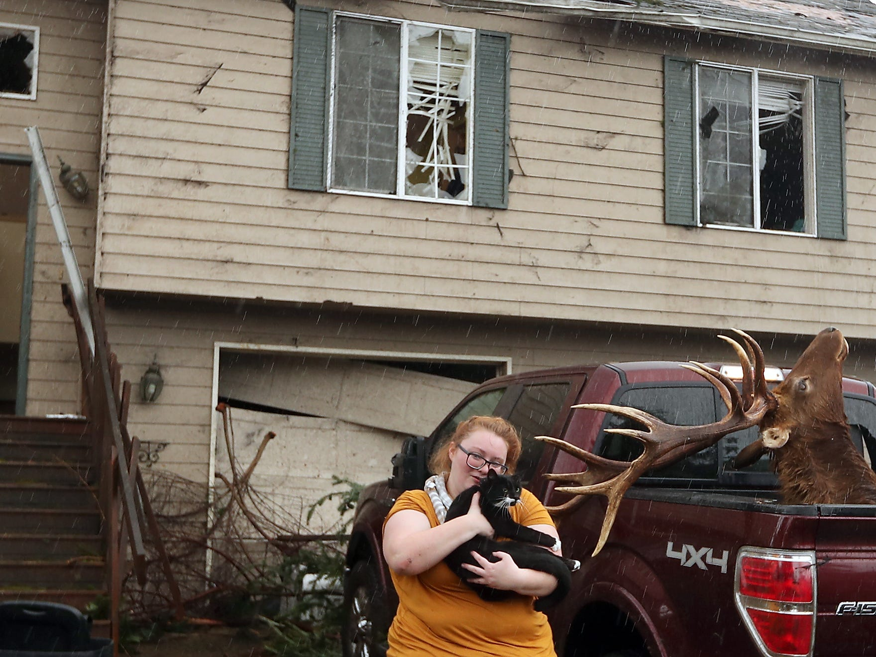 Morgan Crain hurries through the rain as she snuggles her cat Loki after finding him scared and hiding under one of the beds of her family's heavily damaged home in Port Orchard on Wednesday, December 19, 2018. The Crain's are still looking for one of their cats still missing after the storm.