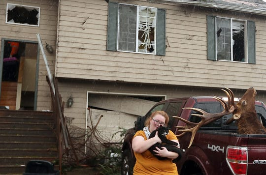 Morgan Cain snuggles her cat, Loki, outside her heavily damaged home on Wednesday. The Crains were still looking for another missing cat.