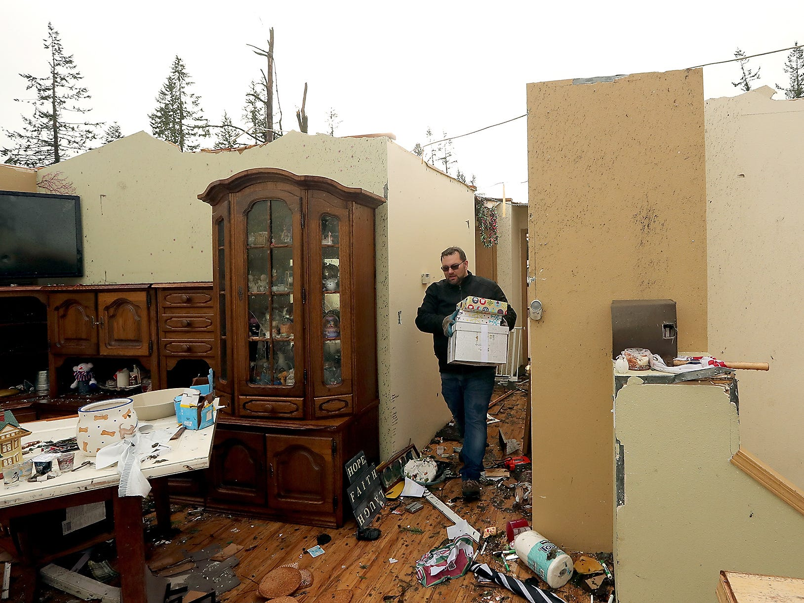 John Mueller carries boxes through the hallway of his now roofless home as he and his family try to salvage what they can from their  home on Tiburon Court in Port Orchard on Wednesday, December 19, 2018.
