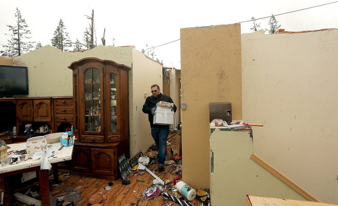 John Mueller carries boxes through the hallway of his now roofless home on Tiburon Court in Port Orchard on Wednesday. Mueller and his family were trying to salvage what they could.