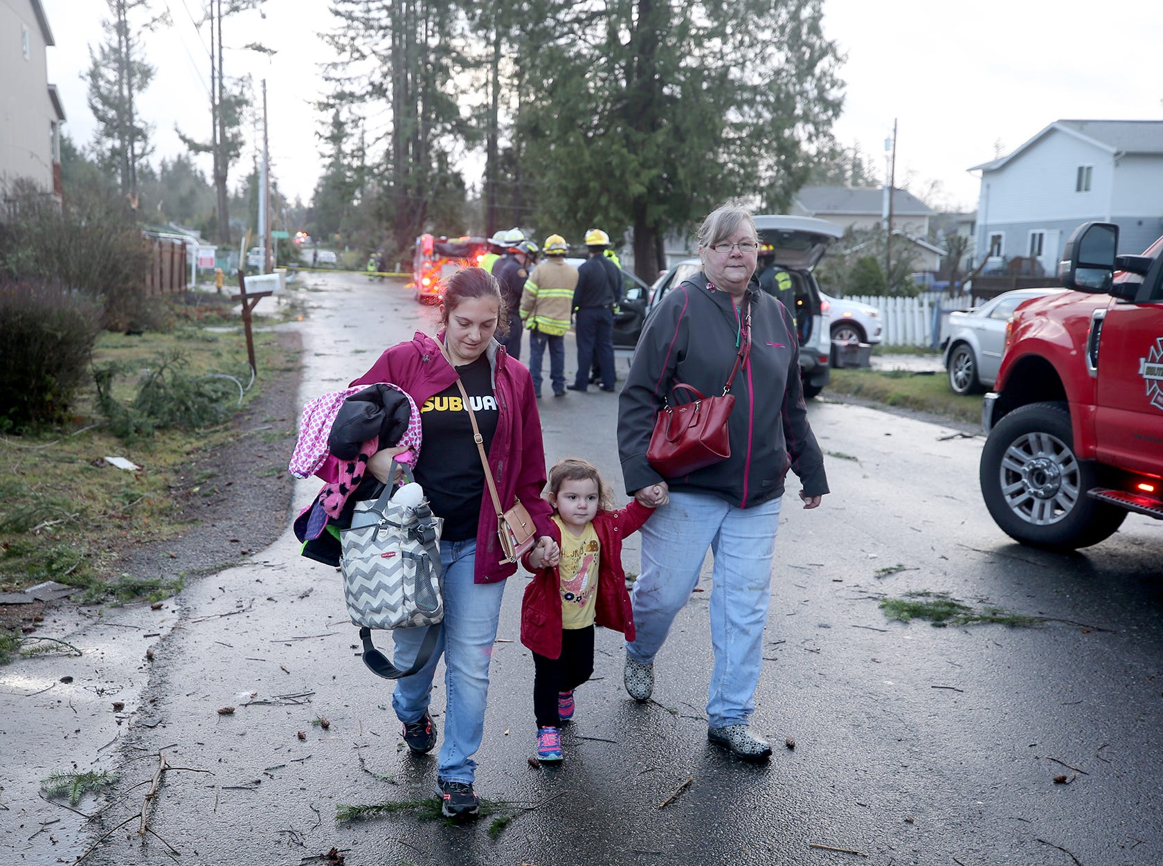 People walk away from their Harris Road neighborhood in Port Orchard after a tornado touchded down there on the afternoon of Tuesday, Dec. 18.