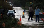 Residents make their way past downed trees as they head down Harris Road SE on Wednesday, December 19, 2018.