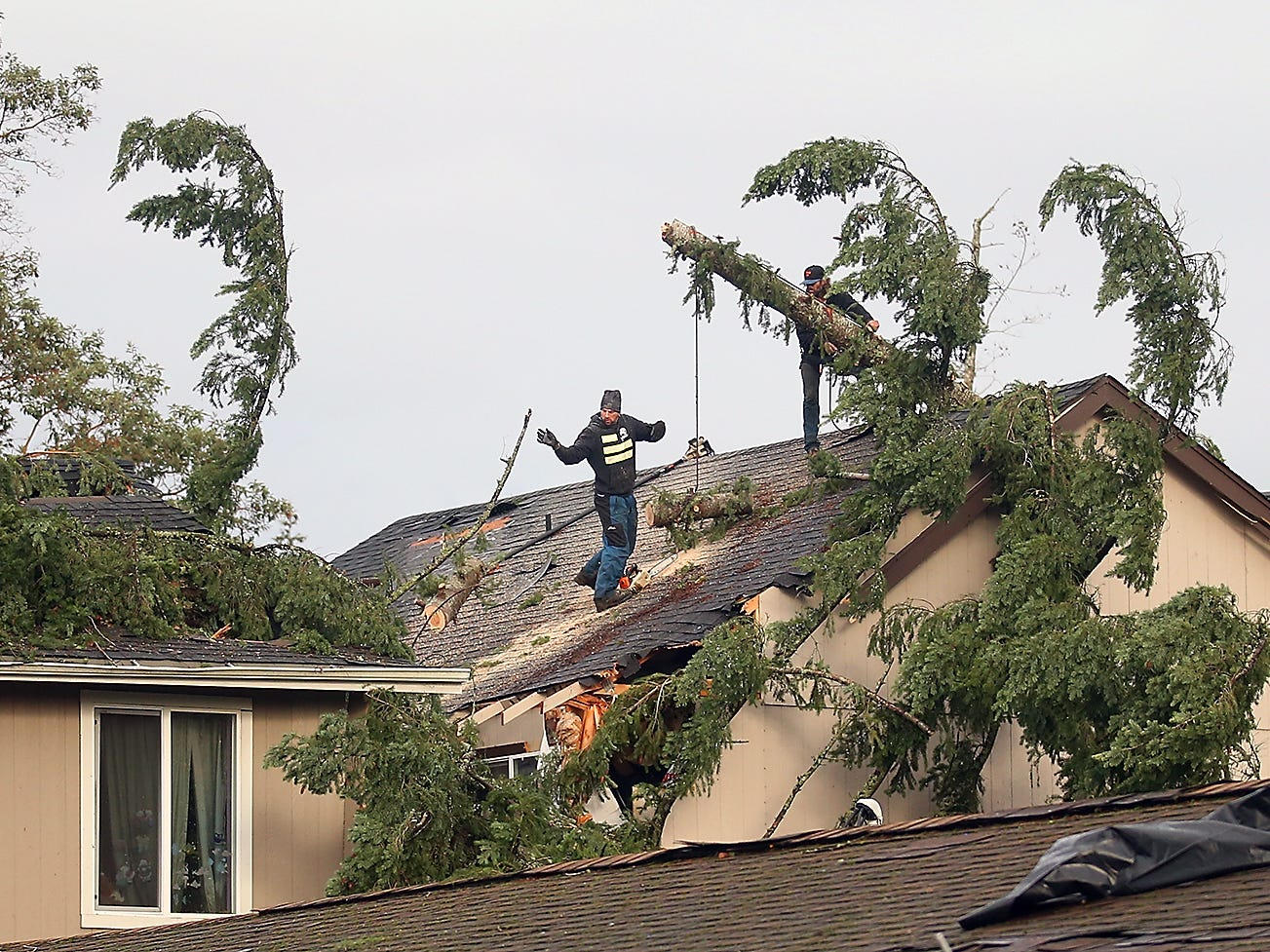 Tree crews work to remove trees from the roofs of homes on SE Upchurch Way in Port Orchard on Wednesday, December 19, 2018.