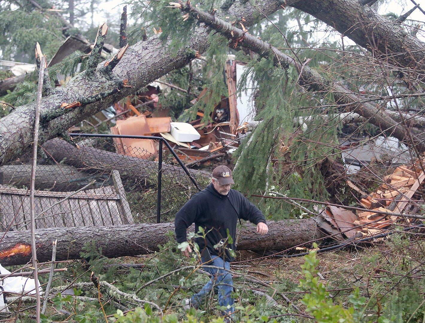 Matt Hargis walks through downed trees behind the Port Orchard Wal Mart after a tornado touched down shortly before 2 p.m. Tuesday, December 18.