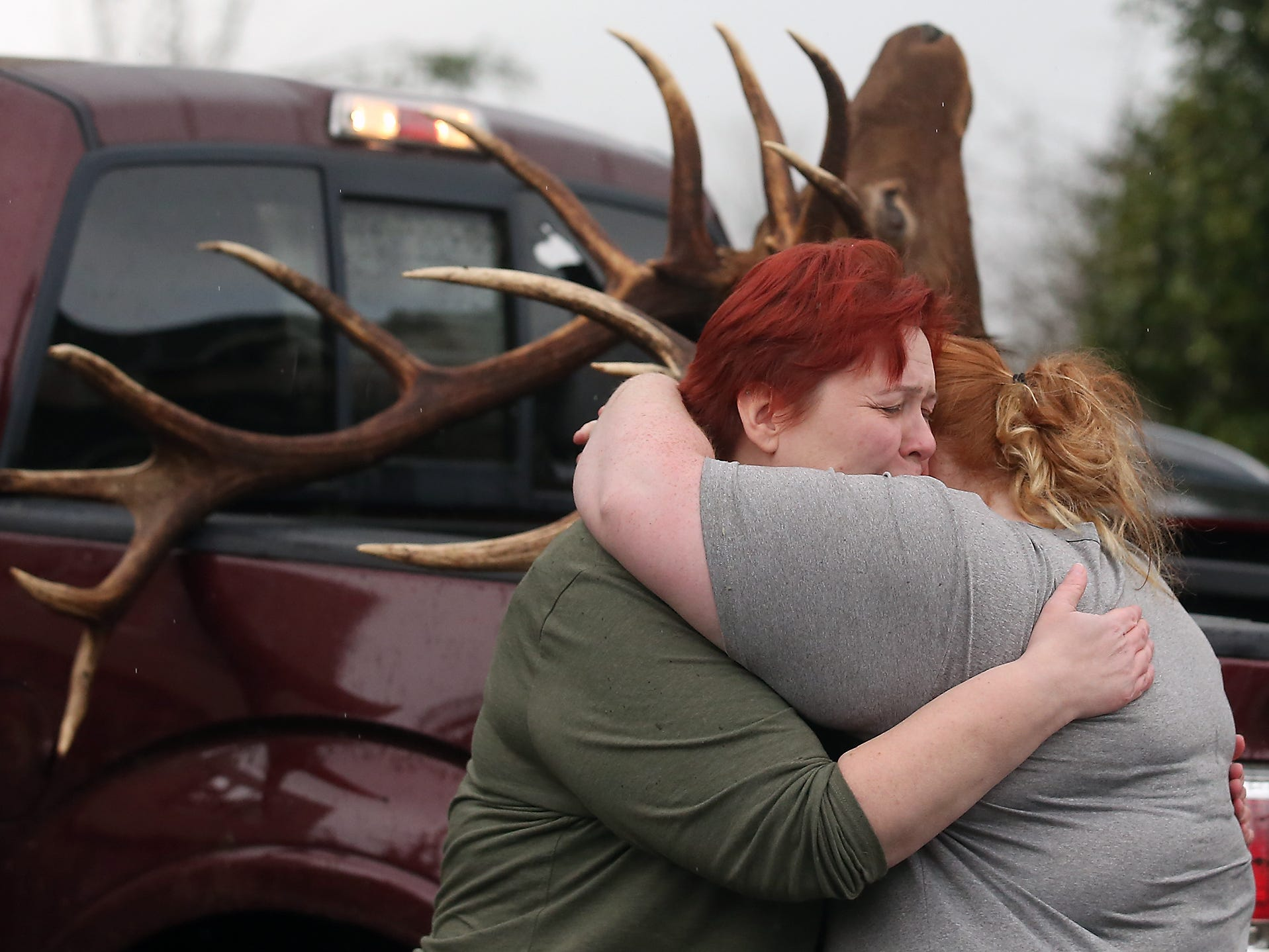 Tawnia Cope-Crain (left) embraces daughter Tamlyn in the driveway of their heavily damages home on Tiburon Court in Port Orchard on Wednesday, December 19, 2018. The taxidermy elk head in the back of the truck behind them was from a wall in their home and was found in the neighbors yard.