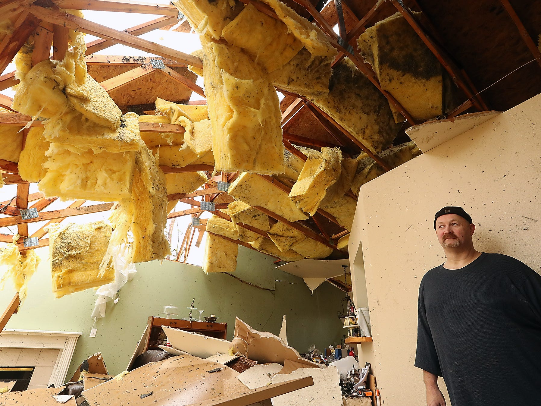 Aaron Crain in the living room of his heavily damaged home on Tiburon Court in Port Orchard on Wednesday, December 19, 2018.