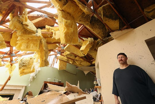 Aaron Crain in the living room of his heavily damaged home on Tiburon Court in Port Orchard on Wednesday, Dec. 19, 2018. The Crain family has struggled with delays in the construction process as they work to rebuild their home.