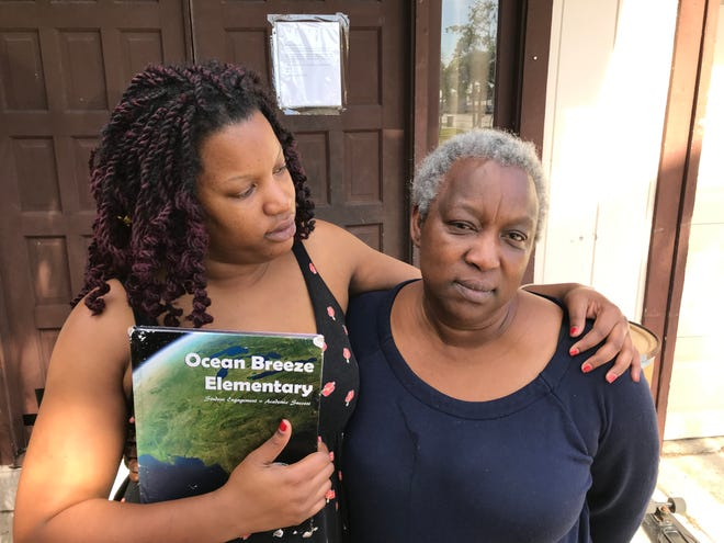 Nichole Brown comforts the grandmother of Gregory and Verdell Morgan