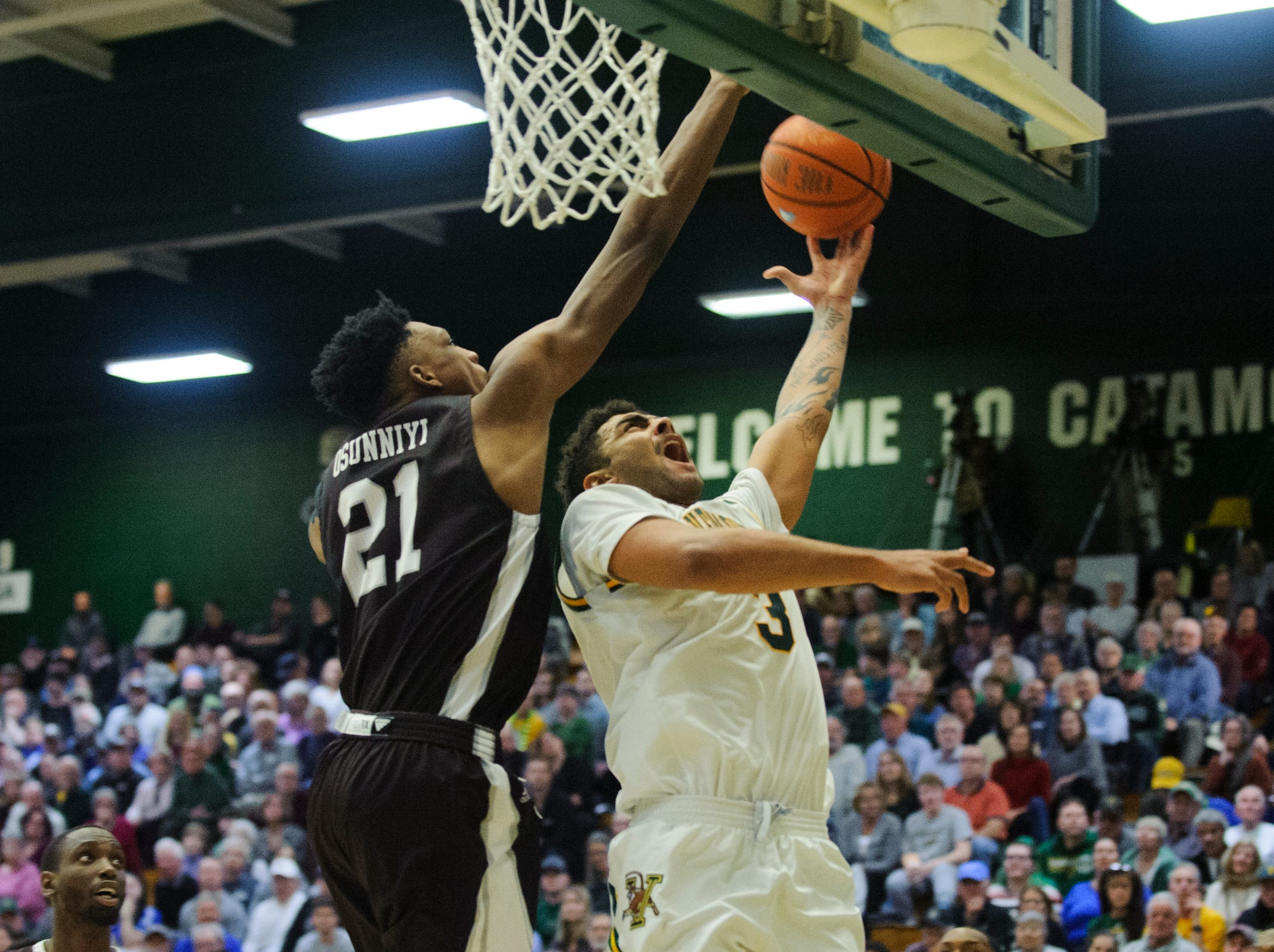 Vermont forward Anthony Lamb (3) leaps past St. Bonaventure's Osun Osunniyi (21) for a lay up during the men's basketball game between the St. Bonaventure Bonnies and the Vermont Catamounts at Patrick Gym on Tuesday night December 18, 2018 in Burlington.