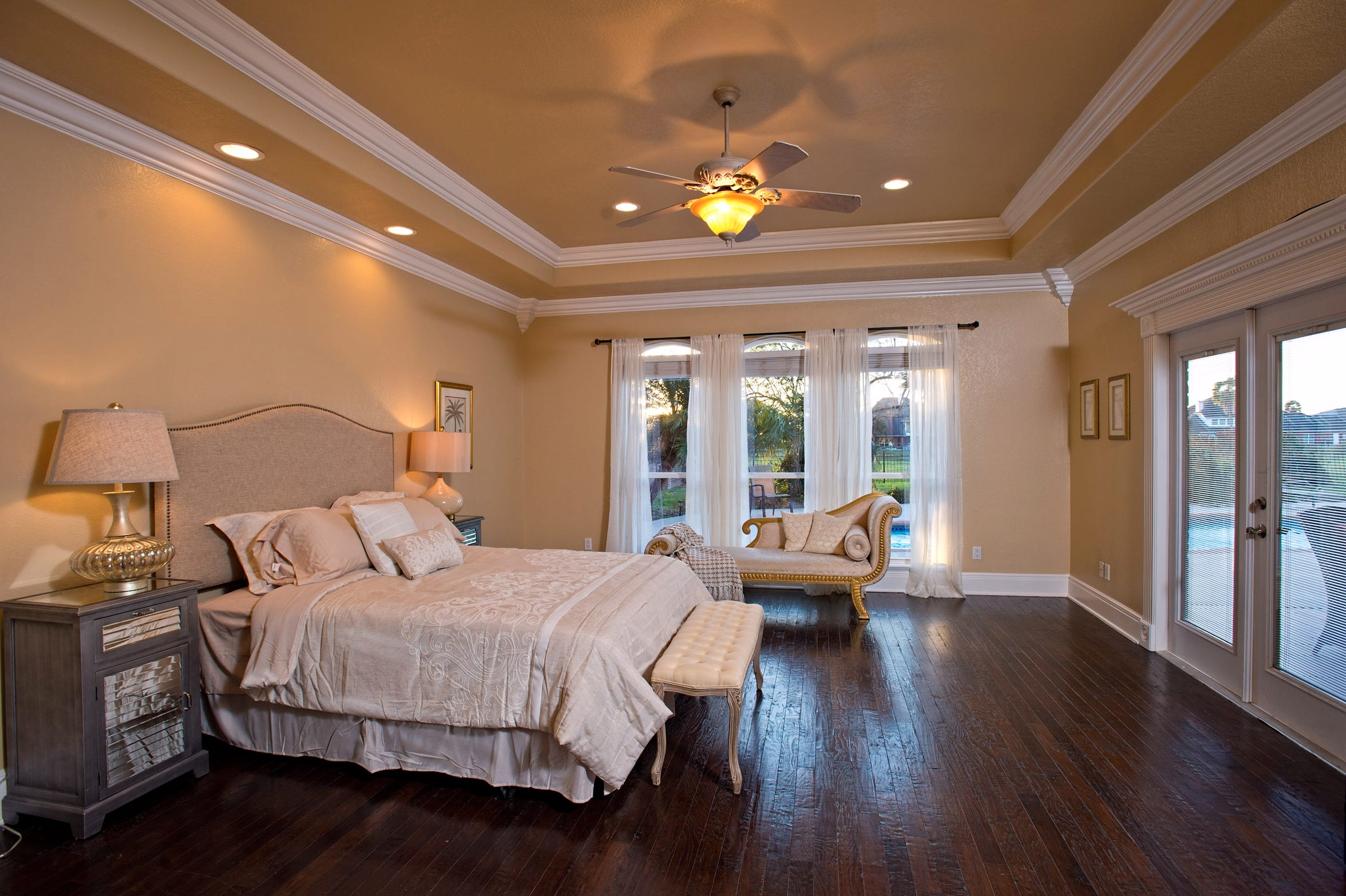 The extra spacious master bedroom takes in views and private access to the pool and yard area.