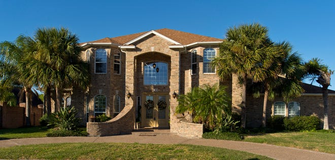 The stately two story home sits in Kings Crossing's gated area, The Domain; at 1 Bar Le Doc West.