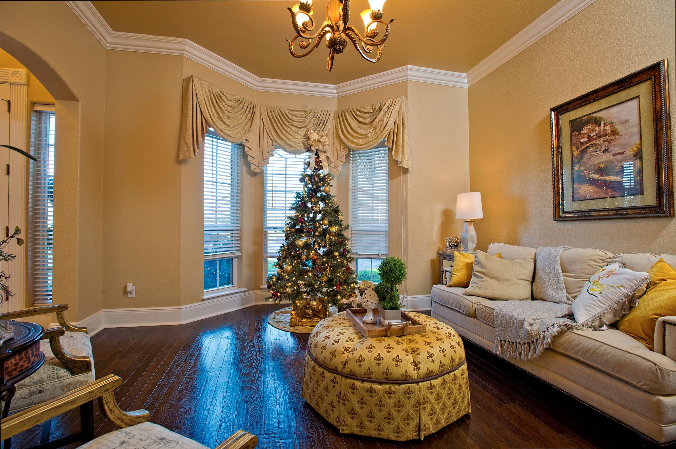 A formal living area just off of the entry foyer features wood floors, thick crown molding and a bay window