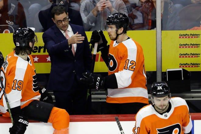 Flyers interim head coach Scott Gordon, center, talks with Nolan Patrick, left, during Gordon's Flyers debut Tuesday night.