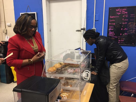 Interim Camden School District Superintendent Katrina McCombs looks over the choices at the Tiger Cafe at Woodrow Wilson High School as Gabriella Council rings up her order.