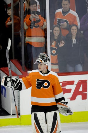 Carter Hart acknowledges the crowd after being named the No. 1 star in his NHL debut.